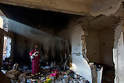 A beam of light shines through the home of Palestinian woman  Ramba Kafanah as she stands breastfeeding her new born baby  in the kitchen of her damaged home in the early morning as she breastfed her newborn baby in Beit Hanoun, Gaza on October 30,2014. Her home was heavily damaged during the recent 50 day war between Israel and the Hamas-controlled Gaza Strip but still lives with her family in the home  . (Photo by Heidi Levine/Sipa Press).