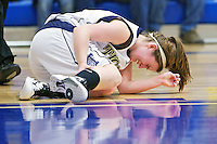 Timberlake High's Syndie Malloy cringes in pain as she grabs her right leg that cramped after sinking a shot as she was falling to the ground in the final overtime of the Tiger's double-overtime win against Snake River High.