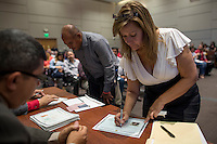 A new U.S. citizen signs her certificate after she become a U.S. citizen during a naturalization ceremony at the Evo A. DeConcini U.S. Courthouse in Tucson, Arizona, U.S., on Friday, Sept. 16, 2016. Photographer: David Paul Morris/Bloomberg