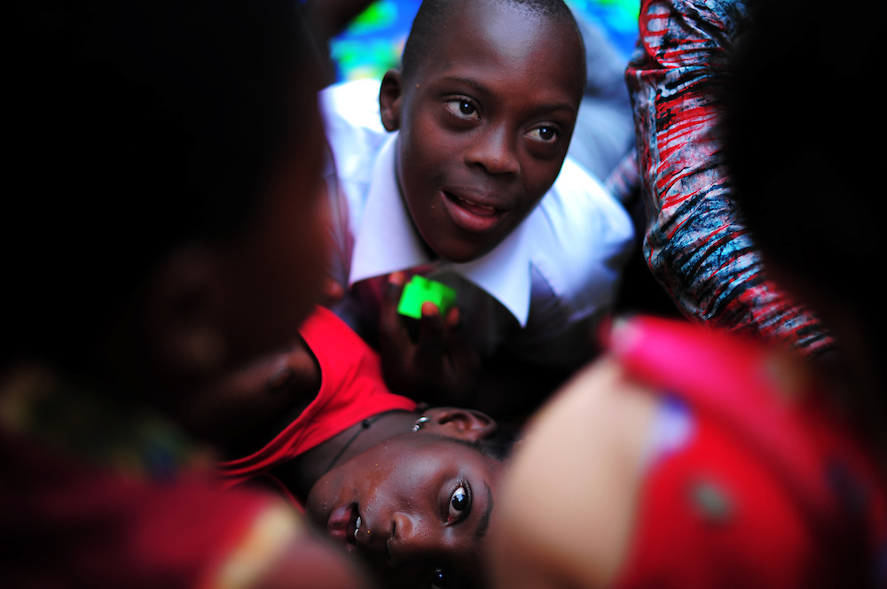 LOME, TOGO - 12-09-19   - Children playing surround CBM's Rika Esser during a visit to a self help group for mothers with disabled children in Lomé, Togo on Wednesday, September 19. Approximately 35 women attend the group, which meets at a local health clinic. Photo by Daniel Hayduk