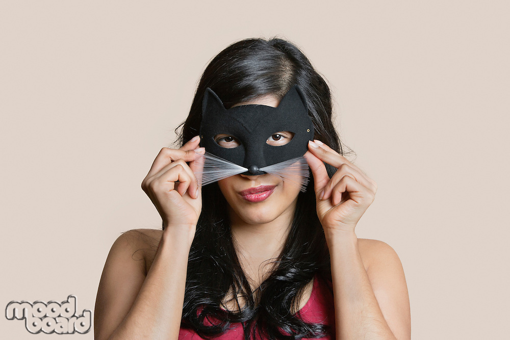 Portrait of a young woman wearing eye mask over colored background
