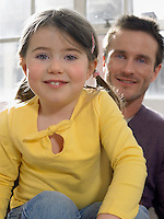 Father and daughter (3-4) smiling indoors (portrait)