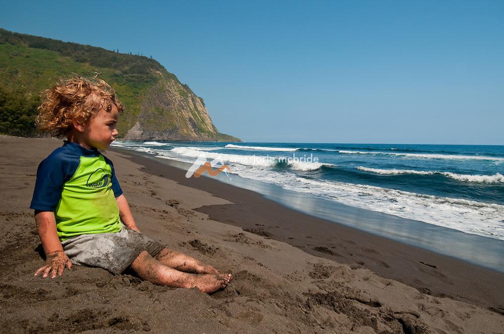 Little boy sitting on the black sand beach. Waipi'o Valley, Hawaii.