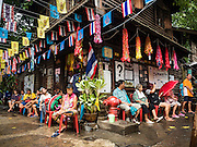 06 OCTOBER 2016 - BANGKOK, THAILAND: Residents of Pom Mahakan Fort take shelter from a monsoon rain under eaves of buildings in the old fort. The residents were waiting for city officials who planned to destroy a home in the community. Evictions are continuing at a slow pace in Pom Mahakan Fort and as people move out their homes are destroyed to ensure new squatters don't move in. More than 40 families still live in the Pom Mahakan Fort community. Bangkok officials are trying to move them out of the fort and community leaders are barricading themselves in the fort. The residents of the historic fort are joined almost every day by community activists from around Bangkok who support their efforts to stay. City officials said recently that they expect to have the old fort cleared of residents and construction on the new park started by the end of 2016.      PHOTO BY JACK KURTZ