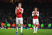 Arsenal Defender Stephan Lichtsteiner (12) and Arsenal Midfielder Matteo Guendouzi (29) thank the crowd after the Europa League group stage match between Arsenal and Sporting Lisbon at the Emirates Stadium, London, England on 8 November 2018.