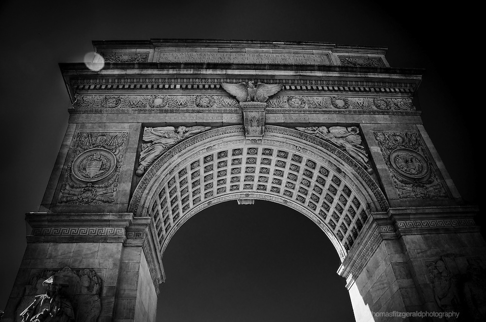 A moody black and white image of the arch in Washington Square Park, New York City