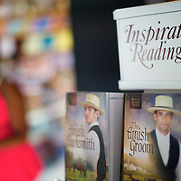 "Novels regarding Amish are on sale at Riehl's Farm and Gift Shop while an Amish girl beckons her sister to their pony in Lancaster County, PA on August 9, 2014.  A bevy of Amish themed reality television shows (Amish Mafia, Breaking Amish, Return to Amish and Amish Haunting - to be televised soon) have prompted controversy over the negative portrayal.  One woman, a Mary Haverstick, a film maker, has launched a website in support of the Amish (respectamish.org) and has garnered the support of 3,000 businesses.  Her motivation to start the website was to ""end the bigoted programming.""  REUTERS/Mark Makela (UNITED STATES)"