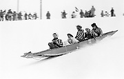 Dave Turnbull, Mr. & Mrs. Hugo Simpson-Wells, and Ben Fenton going down the ski slope on a punt. Dangerous Sports Club ski race. St. Moritz. 1983.<br />