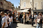 medieval town center with tourist gathering around sales stand La Cite France Carcassonne