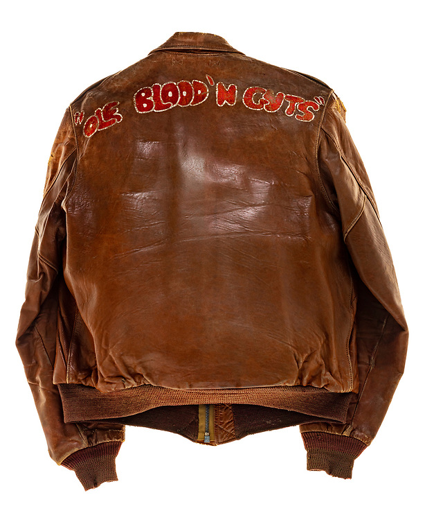 """George D. Hitchcock, a pilot on """"Ole Blood N Guts"""", wore this type A2 flight jacket. Hitchcock was attached to the 570th squadron of the 390th Bomb Group. The 570th squadron insignia patch, a joker with 4 aces laid behind it, is sewn onto the front left of the jacket. Above the squadron patch is the name plate which reads """"LT. G.D. Hitchcock"""". The name """"Ole Blood N Guts"""" is painted on the back of the jacket. """"Ole Blood N Guts"""" flew 35 successful missions. Its 35th and final mission was to Hamburg, Germany, on December 31st, 1944. The aircraft sustained heavy damage while on the mission and it ran off the end of the runway on its return back to base. """"Ole Blood N Guts"""" was salvaged after this mission."""