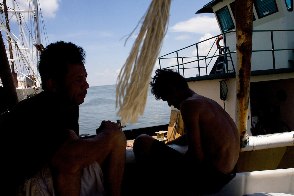 From left, Fishermen Dung Lee, 44, and Hung Tran, 42, wait to ship off on the  H&R shrimp boat at Dean Blanchard Seafood, Inc. in Grand Isle, LA on June 24, 2010 where a fishing ban has been put in place due to the B.P. oil spill. The H&R crew will head west in hopes to find open fishing waters after waiting two months for B.P. to hire their boat.