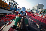 Korean fisherwoman repairing fishing net in Pohang harbor / South Korea, Republic of Korea, KOR, 04 October 2009.