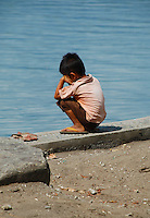 Small boy crouched down looking at the river in west Bali, Indonesia.