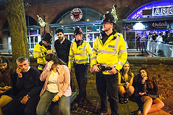 "© Licensed to London News Pictures . 19/12/2015 . Manchester , UK . Police officers detain a man after another man is punched , at Deansgate Locks . Revellers in Manchester enjoy "" Mad Friday "" - also known as "" Black Eye Friday "" - the day on which emergency services in Britain are typically at their busiest , as people head out for parties and drinks to celebrate Christmas . Photo credit : Joel Goodman/LNP"