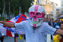 An England fan in a giant skull with the Cross of St George emblazoned it makes his way through Leicester Square, for once not thick with crowds. London, July 11 2018.