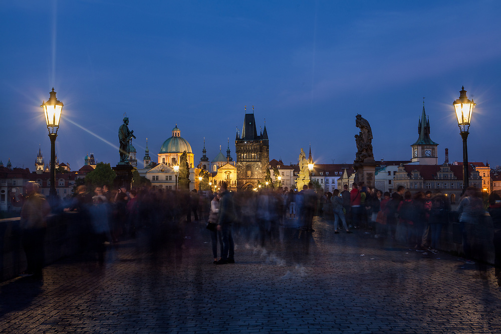 Crowds visiting during the evening Charles Bridge which is a historic bridge that crosses the Vltava river in Prague and one of the main attractions in the city. Its construction started in 1357 under the auspices of King Charles IV and finished in the beginning of the 15th century.