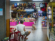 16 JUNE 2016 - PAKSE, CHAMPASAK, LAOS:  A dog begs from a man in Champasak Plaza, a new indoor market in Pakse. Pakse is the capital of Champasak province in southern Laos. It sits at the confluence of the Xe Don and Mekong Rivers. It's the gateway city to 4,000 Islands, near the border of Cambodia and the coffee growing highlands of southern Laos.     PHOTO BY JACK KURTZ