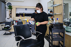 © Licensed to London News Pictures. 30/06/2020. London, UK. A member of staff in Cheriee on Green Lanes in Harringay, north London, cleans the chair as Cheriee prepares to reopen on 4 July. Hairdressers across the UK closed on 23 March following the coronavirus lockdown. As coronavirus lockdown restrictions are eased, hairdressers will reopen on Saturday 4 July. Photo credit: Dinendra Haria/LNP