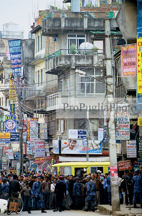 """Bagbazar, 18 February 2005. Armed Police Forces blocking ordinary people from crossing the main road during the nation's Democracy Day. Authorities have once again cut off local telephone lines. """"Today we have arrested several people. They were planning pro-democracy rallies, but we didn't give them any chance to demonstrate"""", a police officer says."""
