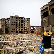"NAGASAKI, JAPAN - AUGUST 8: Tourists look at a part of Hashima Island, commonly known as Gunkanjima or ""Battleship Island"" in Nagasaki Prefecture, southern Japan on August 8, 2017. The island was a coal mining facility until its closure in 1974 is a symbol of the rapid industrialization of Japan, a reminder of its dark history as a site of forced labor during the Second World War. The island now is recognized as UNESCO's World Heritage sites of Japan's Meiji Industrial Revolution. (Photo: Richard Atrero de Guzman/NURPhoto)"