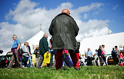 © Licensed to London News Pictures.26/08/15<br /> Egton, UK. <br /> <br /> A man sits on a shooting tick as crowds pass him by at the 126th Egton Show in North Yorkshire. <br /> <br /> Egton is one of the largest village shows in the country and is run by a band of voluntary helpers. <br /> <br /> This year the event featured wrought iron and farrier displays, a farmers market, plus horse, cattle, sheep, goat, ferret, fur and feather classes. There was also bee keeping, produce and handicrafts on display.<br /> <br /> Photo credit : Ian Forsyth/LNP