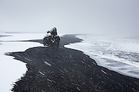 Arnardrangur sea stack in winter. Overlooking Reynisfjara black sand beach towards east from the lower part of Dyrhólaey Peninsula, South Iceland.