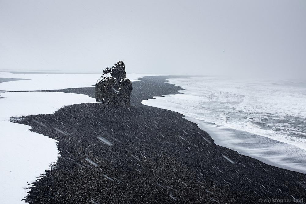 Arnardrangur sea stack in winter. Overlooking Reynisfjara black sand beach towards east from the lower part of Dyrhólaey Peninsula, South Iceland.