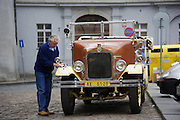 A guide polishes his vintage automobile used for sightseeing tours in the Little Quarter of Prague, Czech Republic.
