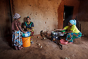 Mforo, Tanzania a village near Moshi, Tanzania.<br /> Solar Sister entrepreneur Fatma Mziray and her eldest daughter Zainabu Ramadhani, 19 cook lunch in her kitchen house using both a clean cookstove using wood and one using coal.  One of her younger daughters, Nasma Ramadhani, age 5 helps out.<br />                                                                     Fatma Mziray is a Solar Sister entrepreneur who sells both clean cookstoves and solar lanterns. Fatma heard about the cookstoves from a Solar Sister development associate and decided to try one out. The smoke from cooking on her traditional wood stove using firewood was causing her to have a lot of heath problems, her lungs congested her eyes stinging and her doctor told her that she had to stop cooking that way. Some days she felt so bad she couldn't go in to cook. Fatma said, &ldquo;Cooking for a family, preparing breakfast, lunch and dinner I used to gather a large load of wood every day to use. Now with the new cook stove the same load of wood can last up to three weeks of cooking. <br /> <br /> &ldquo;With the extra time I can develop my business. I also have more time for the family. I can monitor my children&rsquo;s studies. All of this makes for a happier family and a better relationship with my husband. Since using the clean cookstove no one has been sick or gone to the hospital due to flu.&rdquo;  Fatma sees herself helping her community because she no longer sees the people that she has sold cookstoves have red eyes, coughing or sick like they used to be. She has been able to help with the school fees for her children, purchase items for the home and a cow.<br /> <br /> &ldquo;What makes me wake up early every morning and take my cookstoves and go to my business is to be able to take my family to school as well as to get food and other family needs.&rdquo;