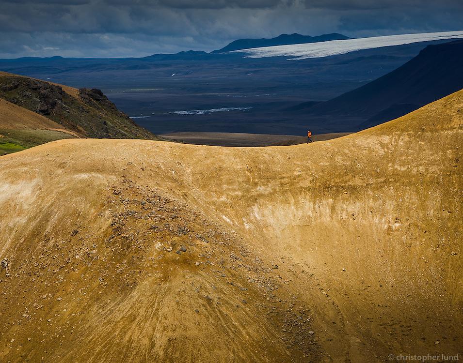 Hiker in Kerlingarfjöll Mountain Range, Interior of Iceland. Hofsjökull Glacier in background.
