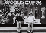 Two Friends stand in front of a display for the 1986 World Cup, London, UK, 1986.