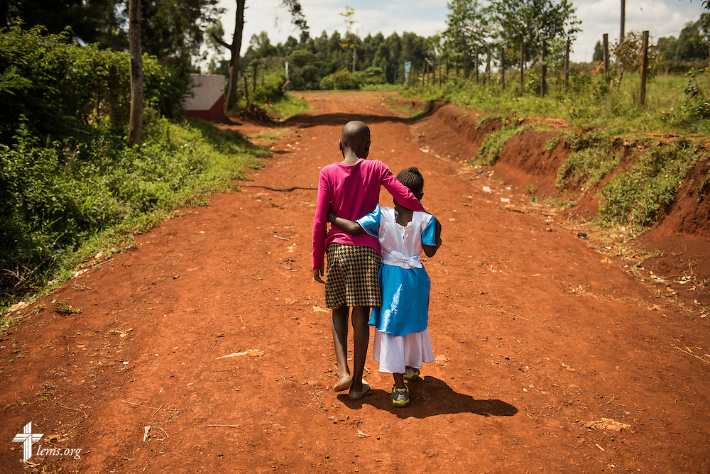 Young girls walk together Sunday, Oct. 18, 2015, on a side road in Kisumu, Kenya. LCMS Communications/Erik M. Lunsford