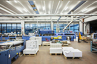 SOVERIA MANNELLI, ITALY - 17 NOVEMBER 2016: Pallets of printed sheets of paper and typographic machine are seen here at the Rubbettino Publishing House in Soveria Mannelli, Italy, on November 17th 2016.<br /> <br /> Rubbettino Publishing House, founded by Rosario Rubbettino in 1973, is of the largest publishing and printing houses in Italy's South. To abate logistical costs and make sure of the production quality, Rubbettino Publishing House built an integrated cycle inside its large warehouse inside Soveria Mannelli. Over 80 employees edit, print and package 300 new books a year for the Italian market, generating a turnover of 8 million euros.<br /> <br /> Soveria Mannelli is a mountain-top village in the southern region of Calabria that counts 3,070 inhabitants. The town was a strategic outpost until the 1970s, when the main artery road from Naples area to Italy's south-western tip, Reggio Calabria went through the town. But once the government started building a motorway miles away, it was cut out from the fastest communications and from the most ambitious plans to develop Italy's South. Instead of despairing, residents benefited of the geographical disadvantage to keep away the mafia infiltrations, and started creating solid businesses thanks to its administrative stability, its forward-thinking mayors and a vibrant entrepreneurship numbering a national, medium-sized publishing house, a leading school furniture manufacturer and an ancient woolen mill.