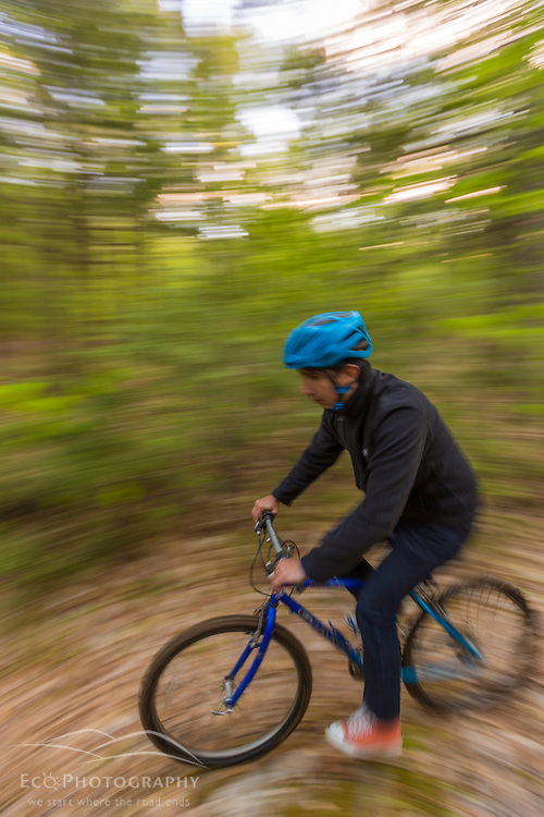 A man mountain biking on a forest trail near Stonehouse Pond in Barrington, New Hampshire.