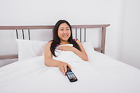 Happy young woman watching TV in bed