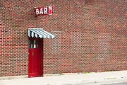 A lone red door along a red brick wall invites patrons. Missoula Photographer
