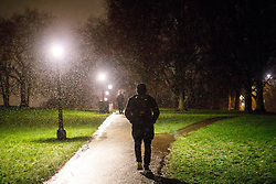 © Licensed to London News Pictures. 12/01/2017. London, UK. People walk on Primrose Hill in north London whilst the first snow of the season starts to fall in London on Thursday, 12 January 2017. Photo credit: Tolga Akmen/LNP