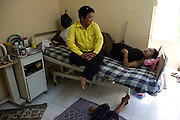 "Ganesh visits his wife Diksha as she lies in her shared surrogate's room on the 3rd floor of the Akanksha Infertility Clinic, Anand, Gujarat, India...Clockwise: Ganesh Gurunja, 28 (yellow, top left); Diksha Gurunja, 28 (top right); 2 boys, 11 and 8 (below).Nepali couple based in Anand, Gujarat..- Ganesh is a merchant operator and earns Rs. 6,000-7,000 a month but is not working right now. He's taking care of the kids and home while Diksha is pregnant with her second surrogacy..- The education expenses of the children are alone Rs. 20,000 a year. .- They used to rent a three-bedroom apt. for Rs. 2,000 per month, which they bought for Rs. 3.5 lakhs with money from Diksha's first surrogacy..- Both the surrogacies were for Japanese couples...Quotes.""You have to lose something to gain something. And what we gain is a lot more than what we lose. For nine months we live like this away from family but with the money, we could get his [Ganesh's] kidney stone operation done, buy a house, a bike, send children to English-medium schools, and eat, wear and sleep well. There are no problems now."" - Diksha..The Akanksha Infertility Clinic is known internationally for its surrogacy program and currently has over a hundred surrogate mothers pregnant in their environmentally controlled surrogate houses. .Photo by Suzanne Lee"