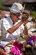 Balinese man wearing a head scarf and holding a flower at his finger tips, Pura Luhur Dalem temple, Penebel, Bali