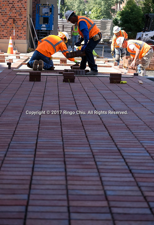 Workers install the bricks in USC's University Village. USC's $700 million shopping and residential complex is nearly complete and more than a dozen retailers (Trader Joe's, Target, Starbucks, etc.) are set to open in August. (Photo by Ringo Chiu)<br /> <br /> Usage Notes: This content is intended for editorial use only. For other uses, additional clearances may be required.