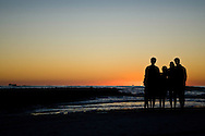 A family enjoys the sunset on Coquina Beach on the southernmost point of Anna Maria Island on Florida's Gulf Coast.