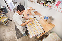 High angle view of young baker preparing bread in bakery