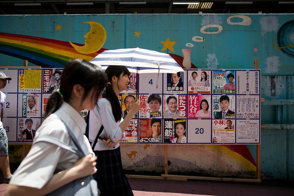 TOKYO, JAPAN - JULY 7 : Japanese students walks past at campaign posters with pictures of candidates for the 2016 Upper House election in Tokyo, Japan on Thursday, July 7, 2016.  The July 10 Upper house election is the first nation-wide election in Japan after government law changes its voting age from 20 years old to 18 years old.(Photo by Richard Atrero de Guzman/NURPhoto)