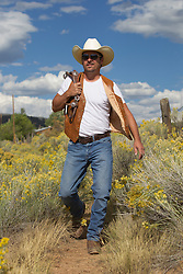 good looking forty something year old cowboy outdoors walking in a field of flowers
