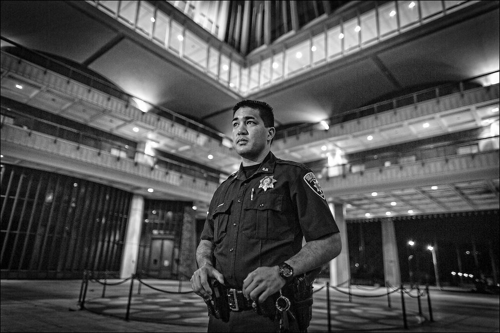 At 12 midnight Deputy Sheriff Blaise Atabay pauses for a moment while checking the scene at the Hawaii State Capitol.
