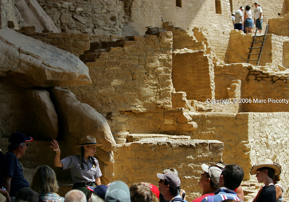 "Park Ranger Amanda Kuhnel (cq, lower left), 23, points out some of the features of the Cliff Palace dwelling during an hour-long tour at Mesa Verde National Park near Cortez, Co. on Wednesday June 28, 2006. It is Kuhnel's first year working at the park and said the National Park Service had hired additional interpretive guides in the park this summer to handle the increased number of visitors for its 100th birthday. She said, ""my tours have all been sold out"". On June 29, 1906 Theodore Roosevelt designated Mesa Verde a national park, the first cultural national park in the history of the world. The park will celebrate it's 100th birthday with a weekend of events, dancing, musical entertainment and special tours of some of the cliff dwellings. Cilff Palace is the largest of all the dwellings at Mesa Verde with 150 rooms and 21 kivas..(MARC PISCOTTY/ © 2006)"