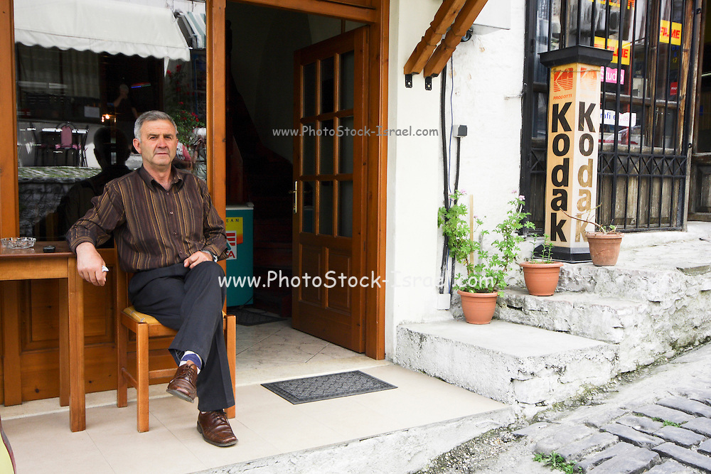 Albania, Libohove man sits in front of his shop