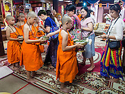 "06 APRIL 2015 - CHIANG MAI, CHIANG MAI, THAILAND:  Family members make merit by presenting alms to boys ordained as Buddhist novices after the boys' ordination on the last day of the three day long Poi Song Long Festival in Chiang Mai. The Poi Sang Long Festival (also called Poy Sang Long) is an ordination ceremony for Tai (also and commonly called Shan, though they prefer Tai) boys in the Shan State of Myanmar (Burma) and in Shan communities in western Thailand. Most Tai boys go into the monastery as novice monks at some point between the ages of seven and fourteen. This year seven boys were ordained at the Poi Sang Long ceremony at Wat Pa Pao in Chiang Mai. Poy Song Long is Tai (Shan) for ""Festival of the Jewel (or Crystal) Sons.  PHOTO BY JACK KURTZ"