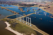 Nederland, Gelderland, Gemeente Nijmegen, 07-03-2010; hoogspanningsmasten aan de oever van de rivier de Waal, de kabels kruisen  de rivier richting elektriciteitscentrale van Electrabel in Nijmegen. Oosterhout aan de horizon..Pylons on the bank of the river Waal, the cables cross the river towards Electrabel power station in Nijmegen .luchtfoto (toeslag), aerial photo (additional fee required).foto/photo Siebe Swart