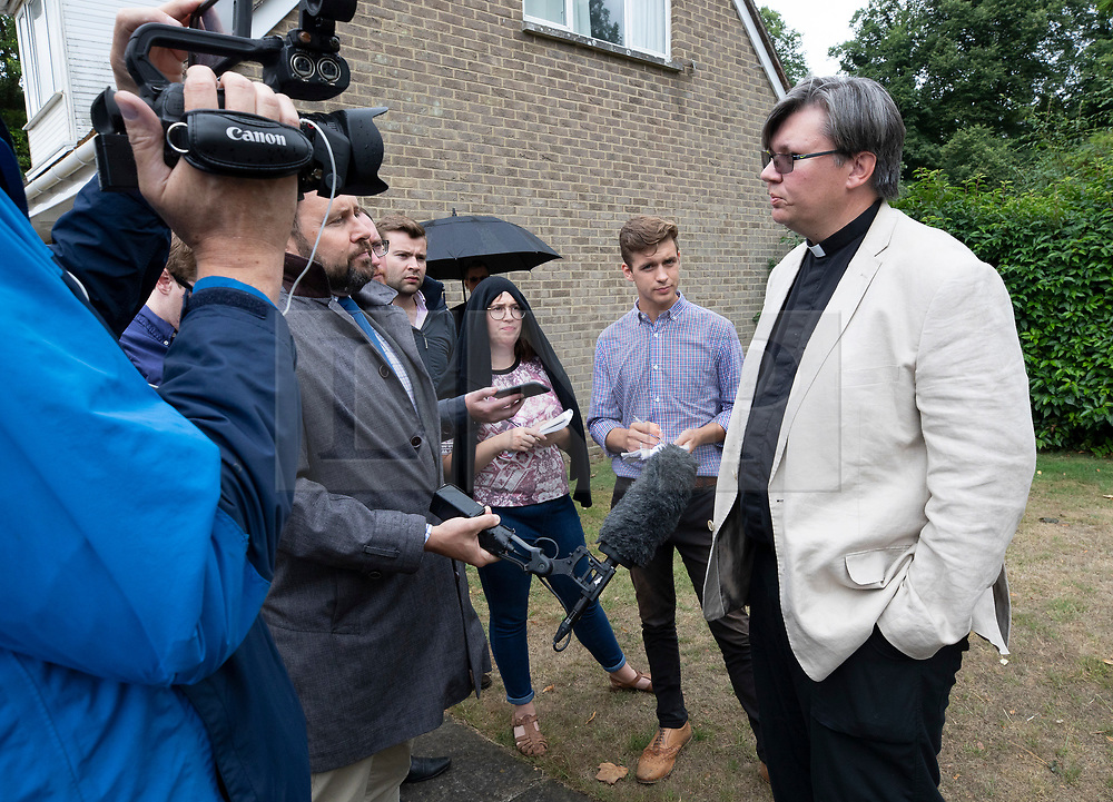 © Licensed to London News Pictures. 30/07/2018. Salisbury, UK. Rev Philip Bromiley (R) talks to reporters after holding the funeral service of Dawn Sturgess, who died on 8 July 2018 after exposure to the nerve agent Novichok. Special safety measures have been put in place to protect mourners attending the ceremony at Salisbury Crematorium. Photo credit: Peter Macdiarmid/LNP